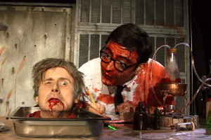 Jesse Merlin as Dr. Carl Hill and a blood-soaked Graham Skipper as Herbert West in RE-ANIMATOR THE MUSICAL, the award-winning live stage production that ran in LA and Las Vegas