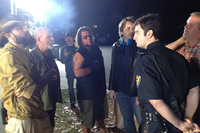 Co-directors John Skipp and Andrew Kasch confer with cast member and DDG podcast guest Graham Skipper (in police uniform) while filming THIS MEANS WAR, an anthology segement appearing in TALES OF HALLOWEEN