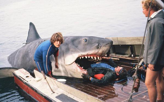 Behind the scenes photo as the mechanical shark, sinking boat and actor Robert Shaw are prepped for Quint's death scene in JAWS.