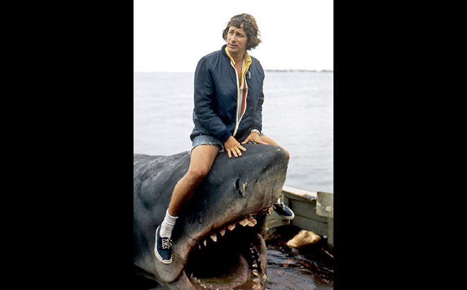 Director Steven Spielberg keeping on top of his mechanical shark during the making of JAWS. Image Credit: Everett Collection