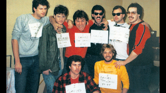 "Tom Savini's make-up crew wearing ""I Survived Tom Savini signs. TOP ROW, LEFT TO RIGHT: Mike Deak, Everett Burrell, John Vulich, Howard Berger, Dave Kindlon, Mike Trcic. BOTTOM ROW, LEFT TO RIGHT: Greg Funk and Greg Nicotero - See more at: https://makeupmag.com/rare-look-zombie-make-day-dead-book/"