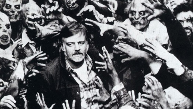 George Romero is surrounded by his undead monsters during production of DAY OF THE DEAD.