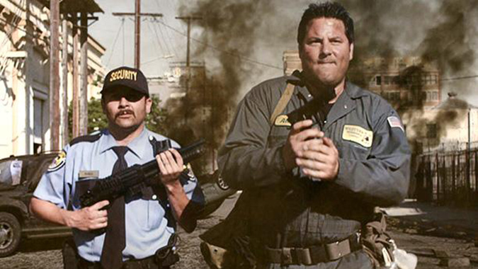 Security guard Jose Ramos (Lombardo Boyar) and exterminator Alex Mathis (Greg Grunberg) lock and load to battle a giant arachnid destroying Los Angeles in Mike Mendez's film BIG ASS SPIDER!