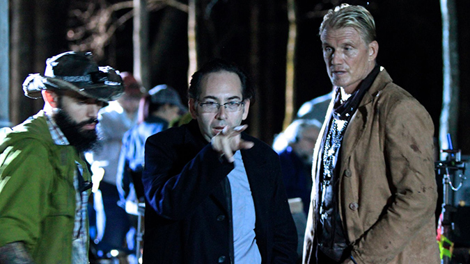 Director Mike Mendez (center) sets up a shot with actor Dolph Lundgren (right) on the set of DON'T KILL IT.