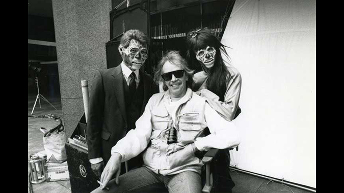 Director John Carpenter takes a break from filming his prescient sci-fi action tale THEY LIVE, flanked by two of the films' repulsive alien characters.