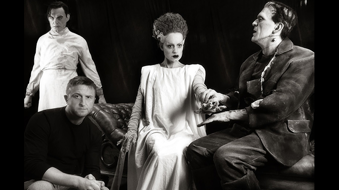 Artist Mike Hill posing with his life-size figures of Henry Frankenstein, The Bride and Frankenstein's monster.
