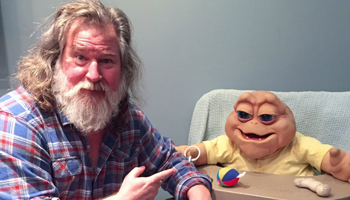 Writer/designer Kirk Thatcher poses with Baby Sinclair from the TV series DINOSAURS.