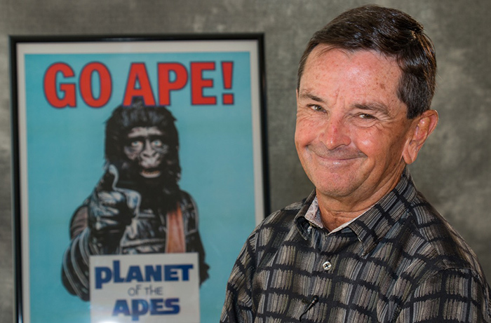 "Actor Bobby Porter, who played Cornelius in BATTLE FOR THE PLANET OF THE APES poses with a Fox promotional ""GO APE!"" marathon poster."