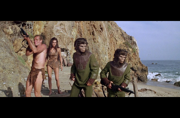 Scene from PLANET OF THE APES as Taylor (Charlton Heston), Nova (Linda Harrison), Cornelius (Roddy McDowall) and Lucius (Lou Wagner) battle Zaius' gorilla troops outside the archeological dig.