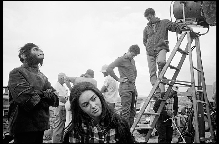 Candid behind the scenes photo of the cast filming PLANET OF THE APES, featuring Lou Wagner (far left) as Lucius and Linda Harrison (lower center) as Nova.