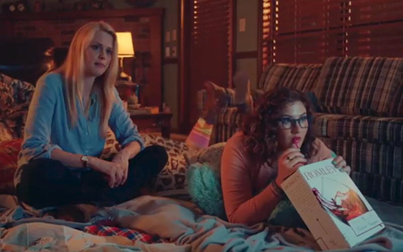 Evie Barret (Janet Varney) and Denise Miller (Deborah Baker Jr.) enjoy a box wine sleepover before the supernatural hits the fan in STAN AGAINST EVIL.